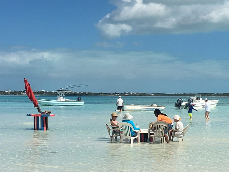 People Sitting at Table in the Beach Water